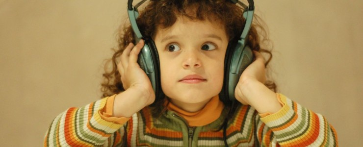 Little kid listening to music on big headphones.
